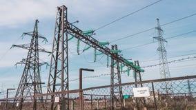 Elektrohulpkantoor met hoog voltage Pylonen met isolatie en draden achter een beschermende omheining Elektrisch en macht stock video