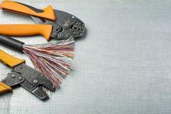 Elektrohulpmiddelen en kabel op metaaloppervlakte met plaats voor tekst Het concept van de energie Stock Afbeeldingen