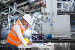 Elektroingenieur die bij controlekamer van thermische elektrische centrale werken stock foto