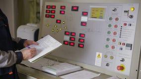 Elektroingenieur die parameters controleren bij een controlebord die van een kerncentrale, waarden schrijven in grafiek schuifsch stock footage