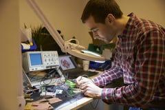 Elektroingenieur Soldering Circuit Board bij het Werkbank stock afbeelding