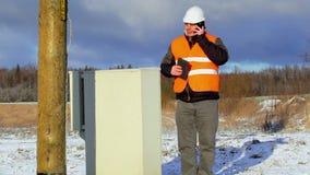 Elektroingenjör med mobiltelefonen nära elektrisk bilaga lager videofilmer