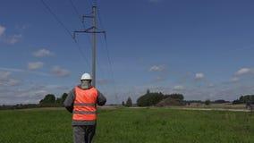 Elektroingenjör som talar på smartphonen under hög-spänning linjer stock video