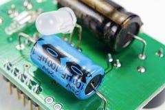Elektrolytiska kondensatorer och LEDD diod på ett bräde för utskrivaven strömkrets royaltyfri bild