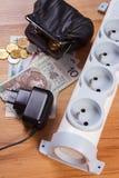 Elektromachtsstrook met losgemaakt stop en poetsmiddelmuntgeld, energiekosten Royalty-vrije Stock Foto's
