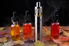 Elektroniczni papierosu i vape ciecze wśród opary na drewnianym stole z jesień liśćmi Zdjęcie Royalty Free