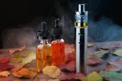 Elektroniczni papierosu i vape ciecze wśród opary na drewnianym stole z jesień liśćmi Obrazy Royalty Free