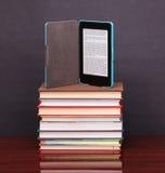 Elektroniczny książkowy czytelnik i palowe stare książki na drewnianym biurku Obraz Stock