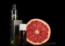 Elektroniczny papieros i aromatyczny ciecz dla dymić, plasterek grapefruitowy zdjęcia stock