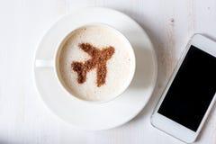 Elektroniczny w rejestraci online Filiżanka kawy z dekoracją cynamonu kształtny samolot zdjęcia stock