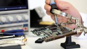 Elektronika inżynier pracuje na obwód desce z lutowniczym żelazem w elektroniki lab zdjęcie wideo