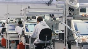 Elektronika inżyniery w biel ubraniach pracuje w lab Inżyniery siedzi przy działaniem na komputerze i stołem obrazy stock