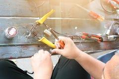 Elektronika technika mężczyźni naprawiają elektrycznych urządzenia Związek łamani druty z lutowniczymi maszynami obrazy stock