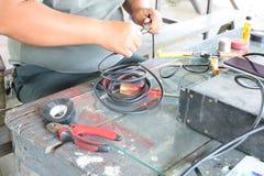Elektronika technika mężczyźni naprawiają elektrycznych urządzenia Związek łamani druty z lutowniczymi maszynami obraz stock