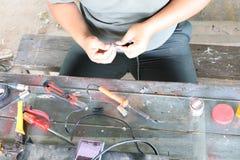 Elektronika technika mężczyźni naprawiają elektrycznych urządzenia Związek łamani druty z lutowniczymi maszynami zdjęcia stock