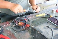 Elektronika technika mężczyźni naprawiają elektrycznych urządzenia Związek łamani druty z lutowniczymi maszynami zdjęcia royalty free
