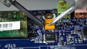 Elektronikareparatie solderende microchips en kringsraad stock videobeelden