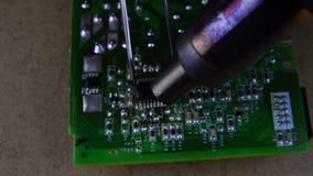 Elektronikreparation som löder, genom att löda stationen av elektroniska delar av brädet arkivfilmer