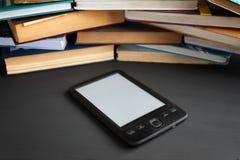 Elektronisch die boek tegenover verscheidene regelmatige handboeken wordt getoond stock fotografie