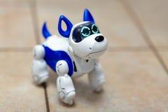 Elektronisch interactief stuk speelgoed hondpuppy op een beige ceramische vloerachtergrond van selectieve nadruk stock afbeeldingen