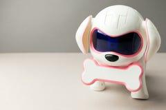 Elektronisch interactief stuk speelgoed hondpuppy op een grijze achtergrond, geavanceerd technisch concept, huisdier van het toek stock afbeelding