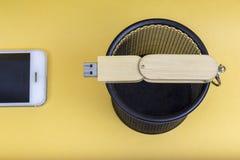 Elektronische Ausrüstungen im Abfalleimer auf gelbem Hintergrund stockfotografie