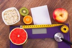 Elektronische badkamersschaal, centimeter en stethoscoop, gezond voedsel, vermageringsdieet en gezond levensstijlenconcept Stock Foto's