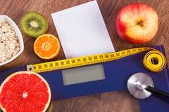 Elektronische badkamersschaal, centimeter en stethoscoop, gezond voedsel, vermageringsdieet en gezond levensstijlenconcept Stock Foto