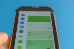 Elektronische Farbpaletten zwischen Smartphone und blauem Hintergrund stockfotos