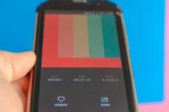 Elektronische kleurenpaletten tussen smartphone en blauwe achtergrond stock fotografie