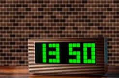 Elektronische klok op de oppervlakte op een bakstenen muurachtergrond stock afbeelding