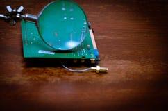 Elektronische Leiterplatte mit gelötetem Kabel Ansicht durch eine Lupe Stockbilder