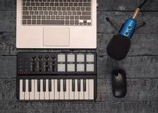 Elektronische muziekmixer, laptop en draadmicrofoon op een zwarte houten lijst Materiaal voor de muziekstudio De mening vanaf de  royalty-vrije stock foto's