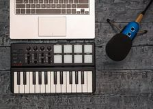 Elektronische muziekmixer, laptop en draadmicrofoon op een zwarte lijst Materiaal voor de muziekstudio de mening van stock afbeelding