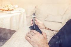 Elektronische sigaret in de handen van een mens die als voorzitter met een mobiele telefoon zit De ruimte van het exemplaar stock foto