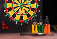 Elektronische sigaret en flessen met vapevloeistof binnen damp op dartboardachtergrond Stock Foto