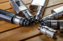 Elektronische sigaret mods voor ecig over een houten achtergrond vape apparaten en sigaret royalty-vrije stock foto