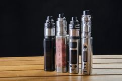 Elektronische sigaret mods voor ecig over een houten achtergrond vape apparaten en sigaret stock afbeelding