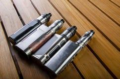 Elektronische sigaret mods voor ecig over een houten achtergrond vape apparaten en sigaret stock foto's