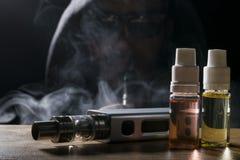 Elektronische sigaret, vaping apparaat met de vloeibare achtergrond van e Stock Foto