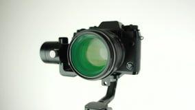 Elektronische steadycam met digitale camera roteert op witte achtergrond stock footage