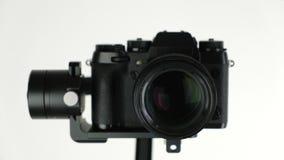 Elektronische steadycam met digitale camera roteert op witte achtergrond stock videobeelden