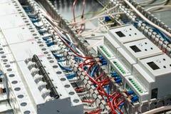 Elektronische und elektrische Geräte auf der Montageplatte des elektrischen Kabinetts Stockbilder