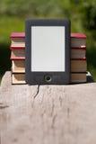 Elektronische und Papierbücher auf Holzbank Stockfotografie