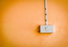 Elektronischer Schalter auf orange Farbwand Lizenzfreies Stockbild