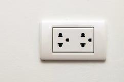 Elektronischer Sockel auf weißer Wand Stockfotografie