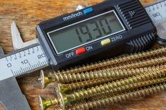 Elektronischer Tasterzirkel Digital mit gelben langen Schrauben am Holztisch in der Werkstattnahaufnahme stockfotografie