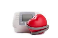 elektronisches Blutdruckmessgerät und rotes Herz Stockbild