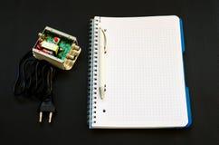 Elektronisches Gerät mit einem Notizbuch und ein Stift nahe bei ihm Stockbild