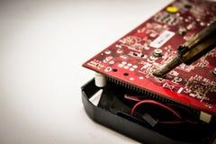 Elektronisches Herstellungs- und Reparaturkonzept - Lötkolben und Mikrokreislauf nahe bei ihm - nah herauf Atelieraufnahme stockbilder